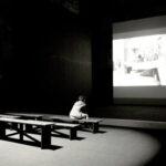 Niño contemplado la pantalla de cine solo en la sala